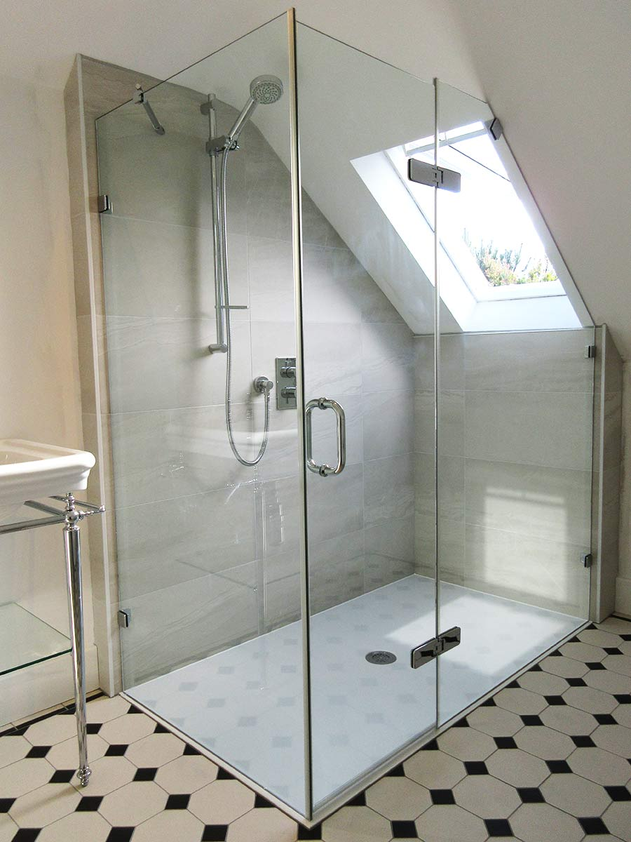 Frameless shower enclosure with angled panel for a loft conversion in Crydon by Room H2o