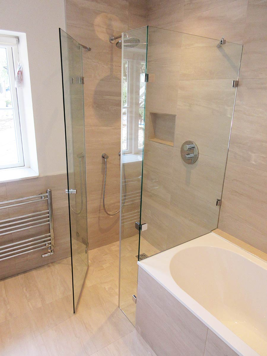 Frameless shower with dwarf side panel created by Room H2o in the space at the end of a bath