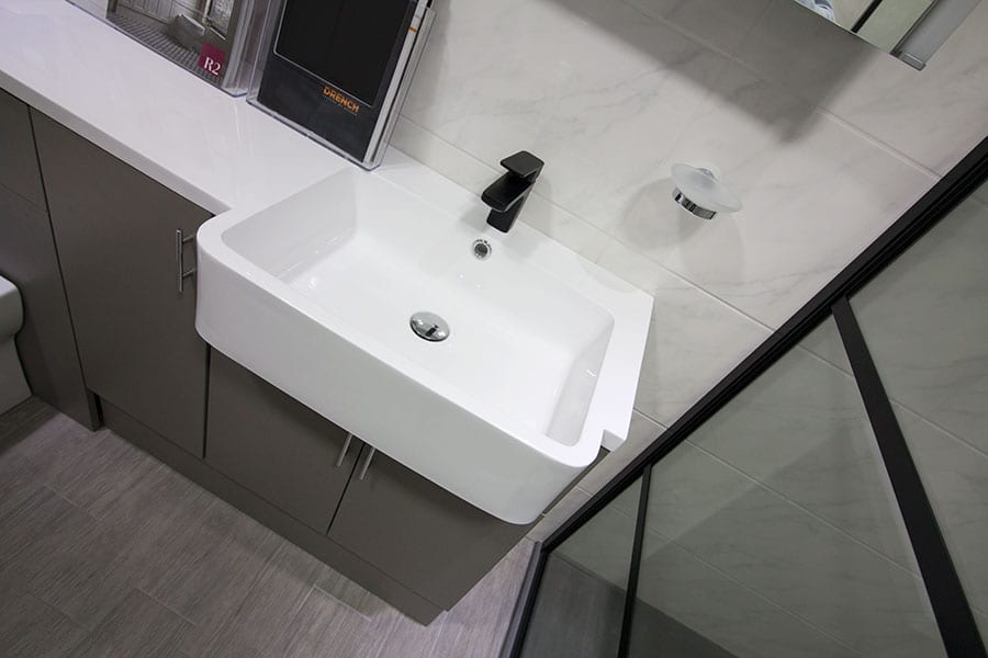 Roper Rhodes olive fitted bathroom furniture with black tap and shower screen on display at Room H2o in Wareham