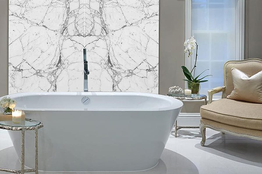 Porcel-Thin book matched white marble porcelain tiles create and eye-catching backdrop for the elegant freestanding bath