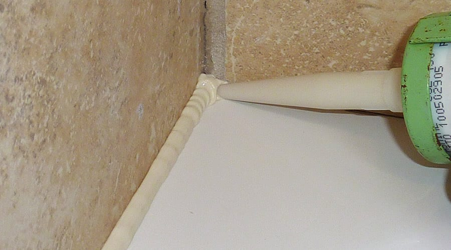 Applying silicone sealant in a continuous bead from the back corner of the shower tray to the front