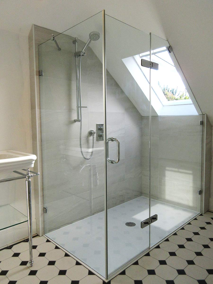 Frameless loft shower enclosure with large angled side panel by Room H2o