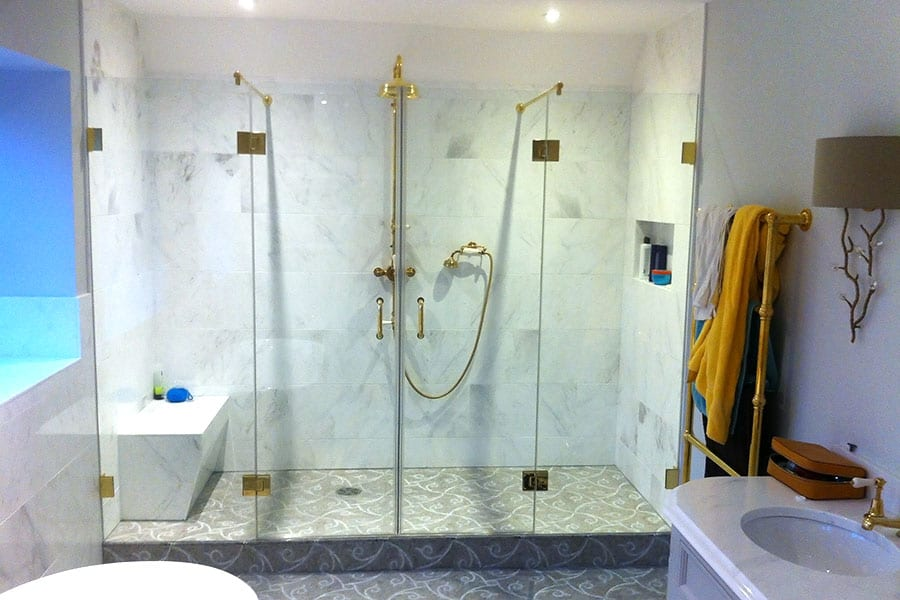 A large frameless shower enclosure with gold fittings in a wetroom by Room H2o