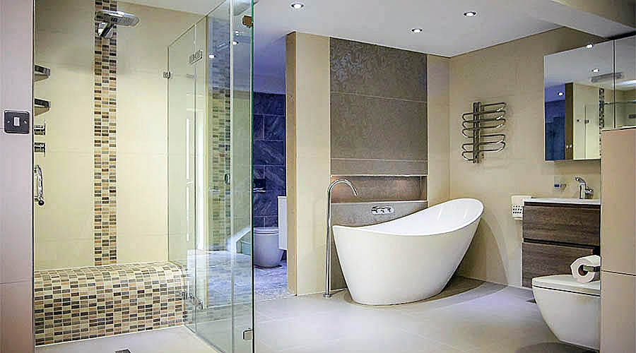 A large frameless glass shower enclosure with wetroom floor and tiled shower seat by Room H2o in Dorset