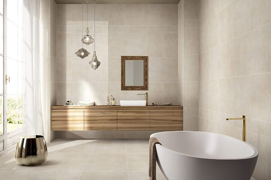 This luxury bathroom features Porcel-Thin matt stone effect porcelain tiles with gold taps and mirror