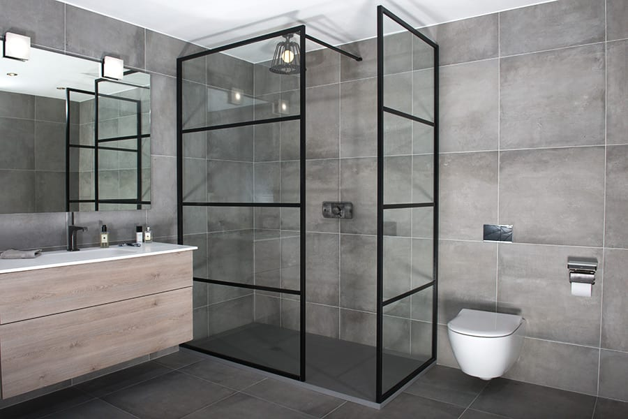 Art deco style custom made black walk in shower screen with return panel by Drench