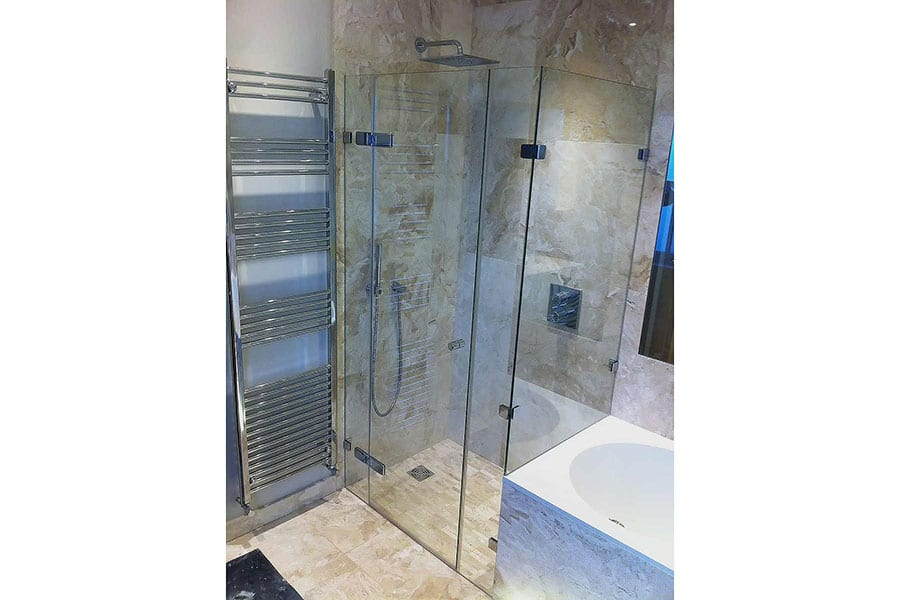 This stylish frameless shower enclosure was created in the space at the end of a bath by Room H2o