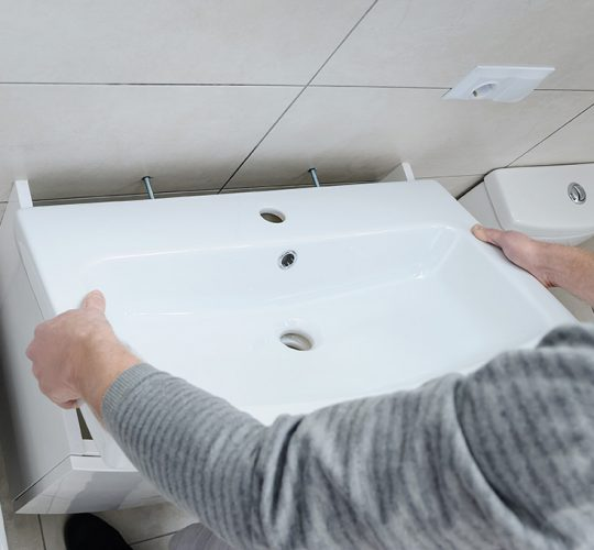 Fitter installing a bathroom sink to wall