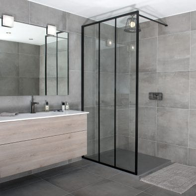 A black art deco inspired LINEA framed shower screen with vertical glazing bars by Drench