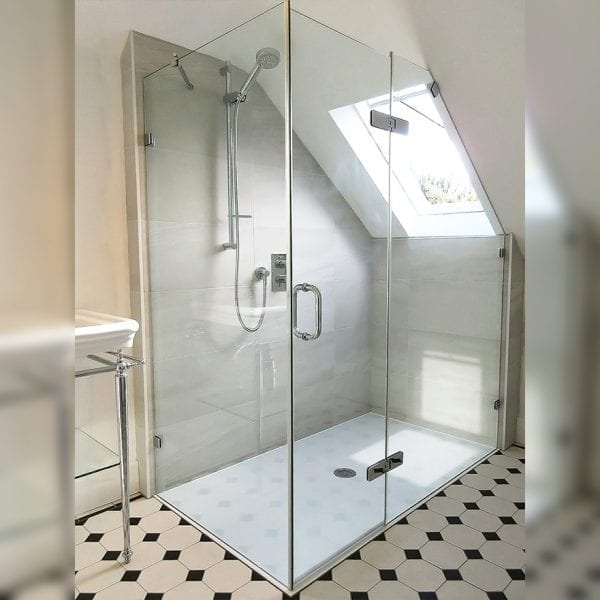 Bespoke frameless corner shower enclosure with angled inline panel by Room H2o in a loft conversion