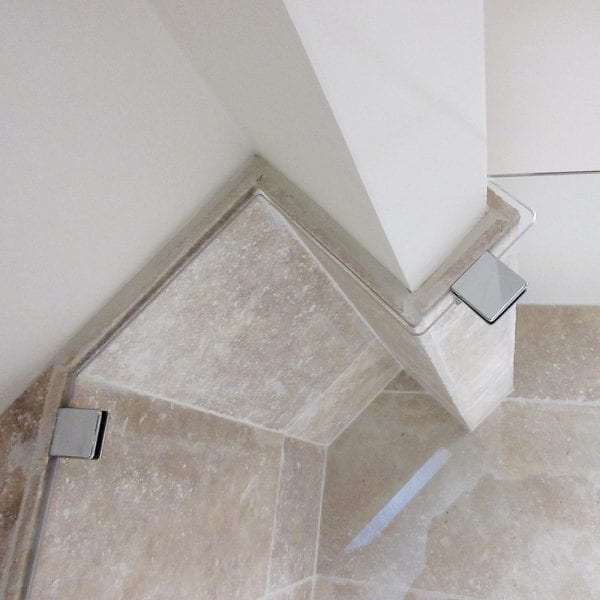 Bespoke framless glass shower screen shaped around the beams of a ceiling