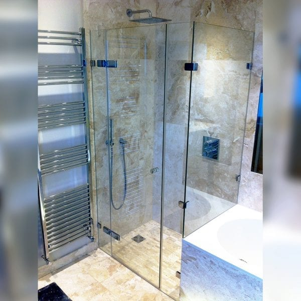 Frameless inline hinged shower door with dwarf side panel over a bath by Room H2o