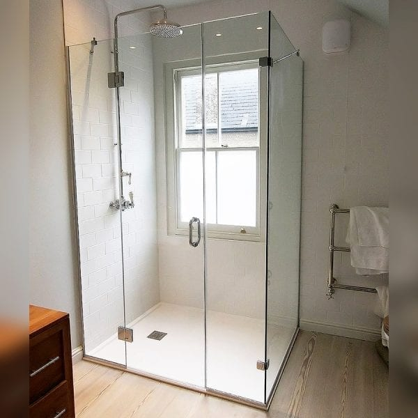 Large frameless hinged shower door between 2 inline panels with side return by Room H2o