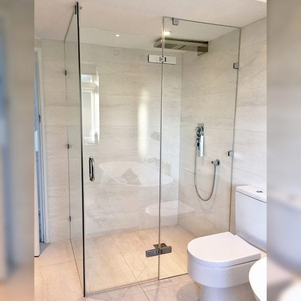 Large frameless corner shower enclosure with glass hinged door by Room H2o