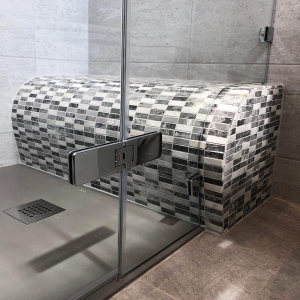Room H2o bespoke frameless shower screen shaped around a tiled shower seat