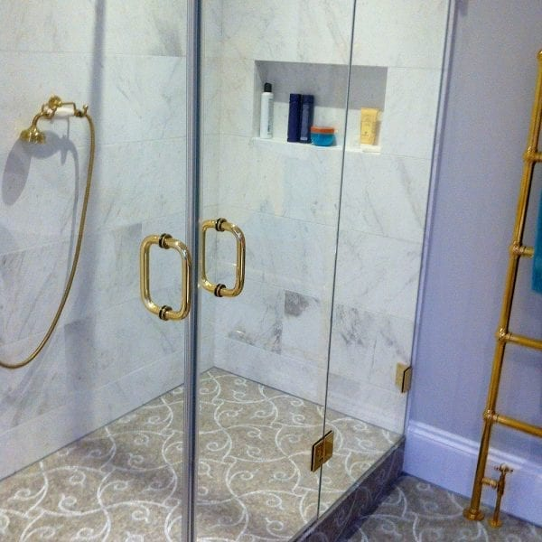 Bespoke frameless hinged shower door with 2 inline panels and gold fittings by Room h2o