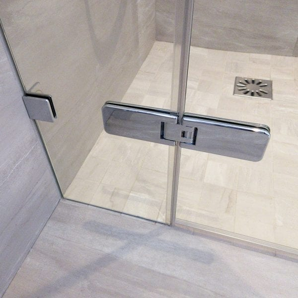 Frameless glass shower door with inline panel with chrome wall brackets and hinges