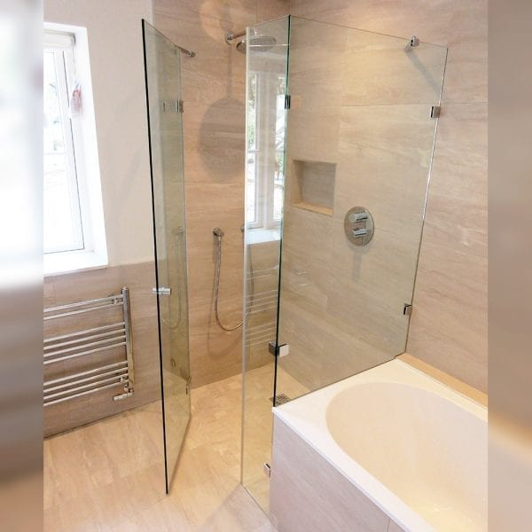 Bespoke frameless shower door with inline panel and dwarf side panel at the end of a bath by Room H2o