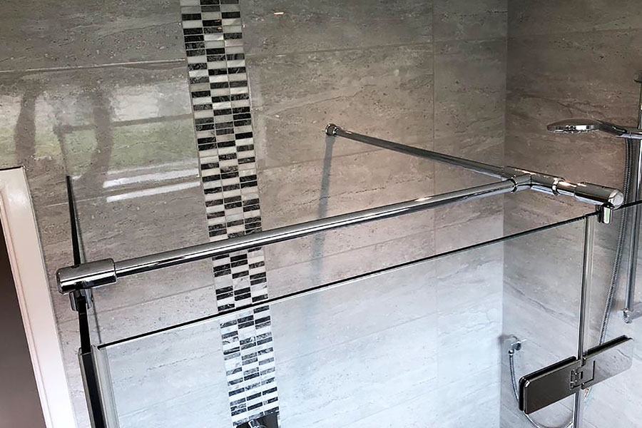 Decorative mosaic tiled boarder designed to match the curved shower seat.