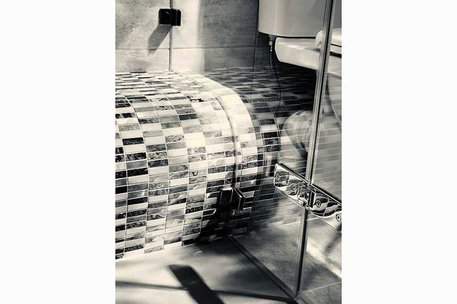 Besoke glass shower screen cut to match a curved shower seat by Room H2o in Dorset