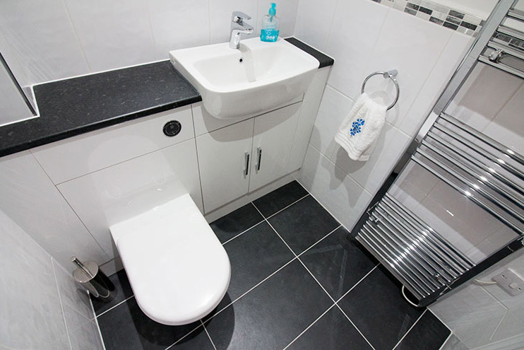 Cloakroom featuring black and white porcelain tiles with Vado fitted furniture and bathroom fittings