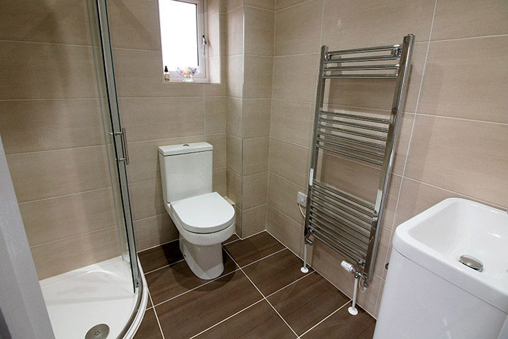 Contrasting brown bathroom tiles and Vado fittings feature in the guest ensuite bathroom
