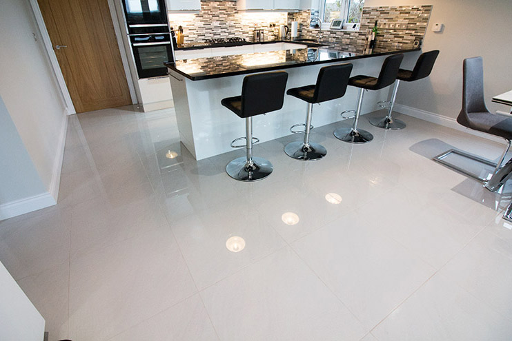 Large kitchen with white polished porcelain floor tiles and mosaic wall tiles