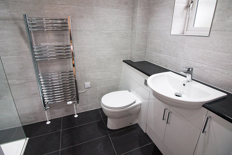 Black and white tiles with gloss white fitted furniture for the master ensuite bathroom