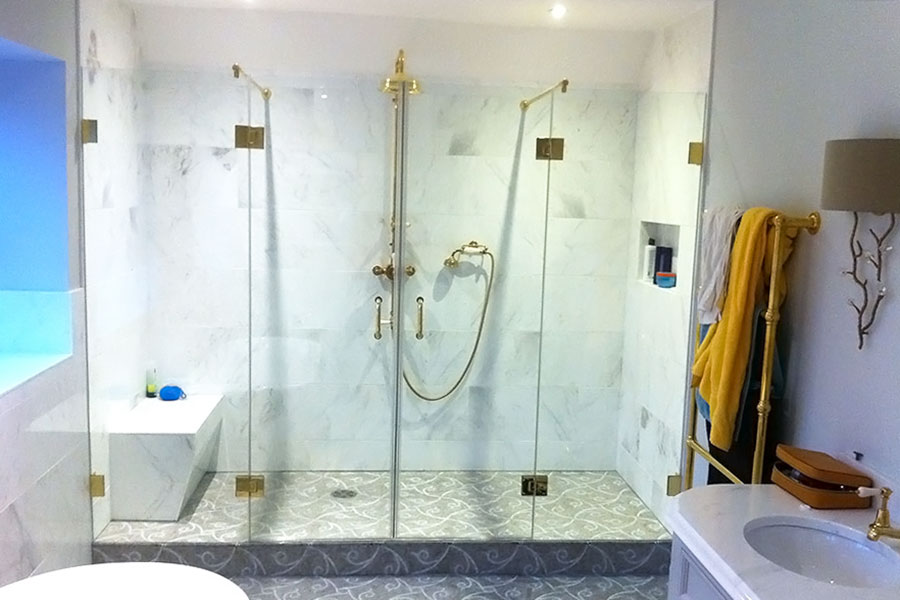 Large frameless shower enclosure with gold handles and fittings