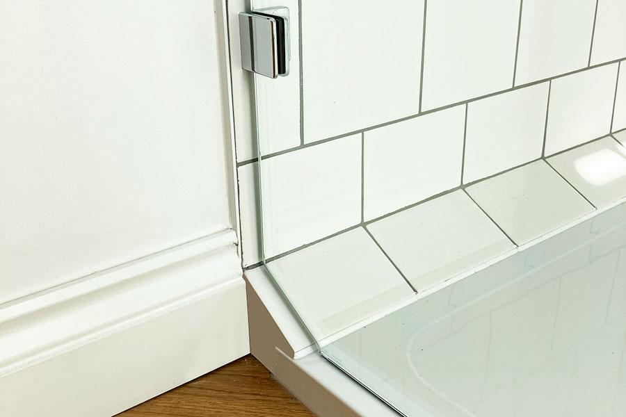 Frameless glass shower screen shaped to match a tiled shower tray detail
