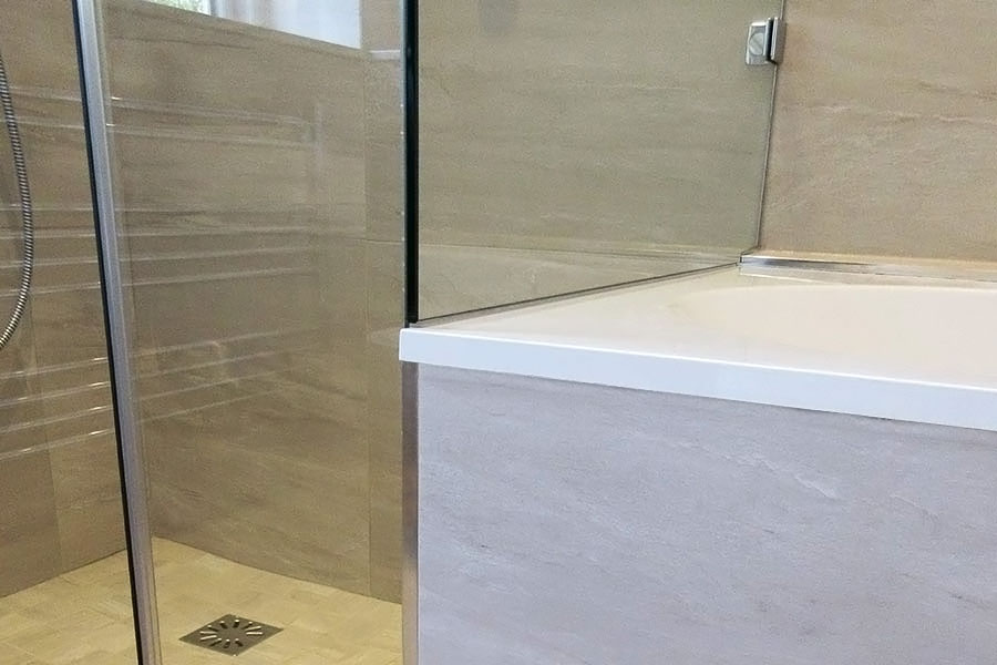 Bespoke frameless glass shower screen made to sit on the end of a bath