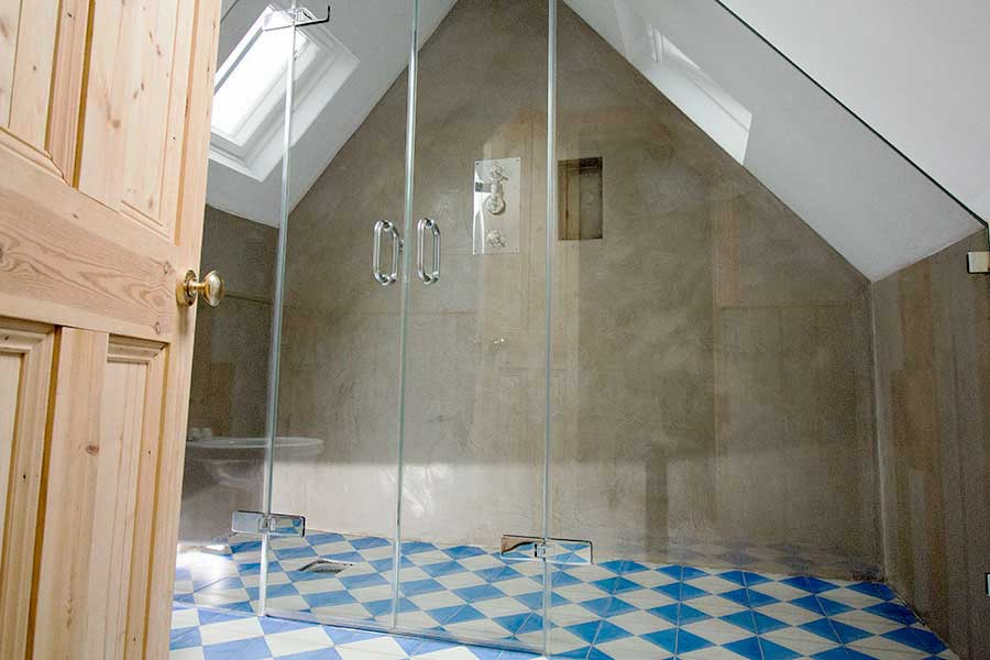 Large bespoke angled frameless shower enclosure shaped to fit the contours of a pitched ceiling by Room H2o